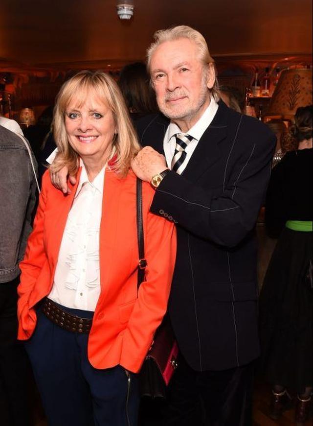 画像: 鮮やかなレッドのジャケットで小粋に。一緒に居るのは、今年で結婚28年目の夫で俳優のリー・ローソン。