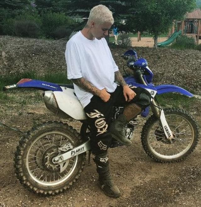 画像: バイクに乗る時は、黒パンツにニープロテクトをしてゴツめのブーツをセット。トップスはシンプルに白Tがキマッてる。