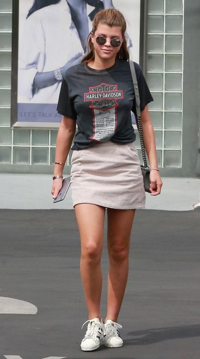 画像: ハーレイ・ダヴィットソンのロゴTシャツをスモーキーピンクのコーデュロイミニスカートに合わせたミスマッチ感がおしゃれ。足元はAdidasのスニーカーでカジュアルに。