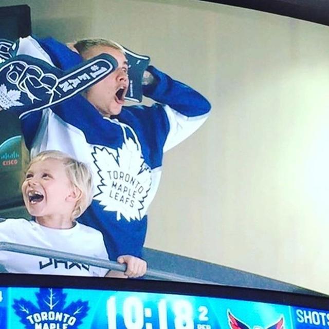 画像: アイスホッケーの観戦中に絶叫するジャスティンと、その横で笑っているジャクソン君。
