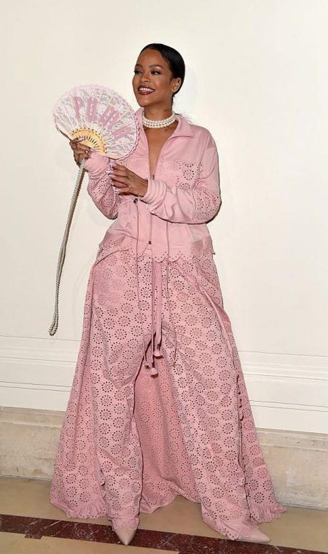 画像: リアーナ自身ももちろん同コレクションのアイテムを着用。ジャージ素材とカットワークレースを組み合わせたピンクのセットアップにパールアクセとレースの扇子でエレガントに。