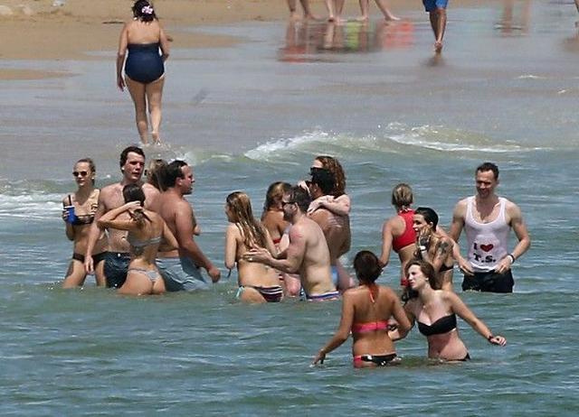画像: モデルのカーラ・デルヴィーニュをはじめ、テイラー軍団が別荘前のビーチで大はしゃぎ。
