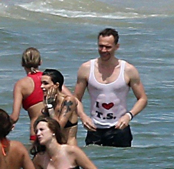 画像: 赤色の水着を着たテイラーの隣に立つトムの胸元には・・・