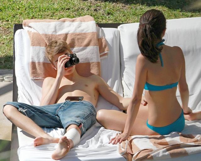 画像: プールサイドではジャスティンがセレーナの水着姿をデジカメで撮影する微笑ましい姿も。