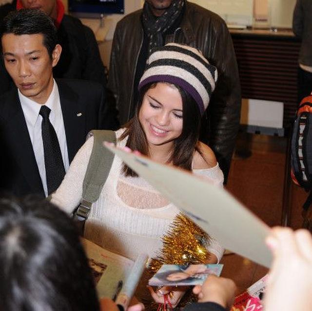 画像: 空港で待っていたファンにサインをするセレーナ。