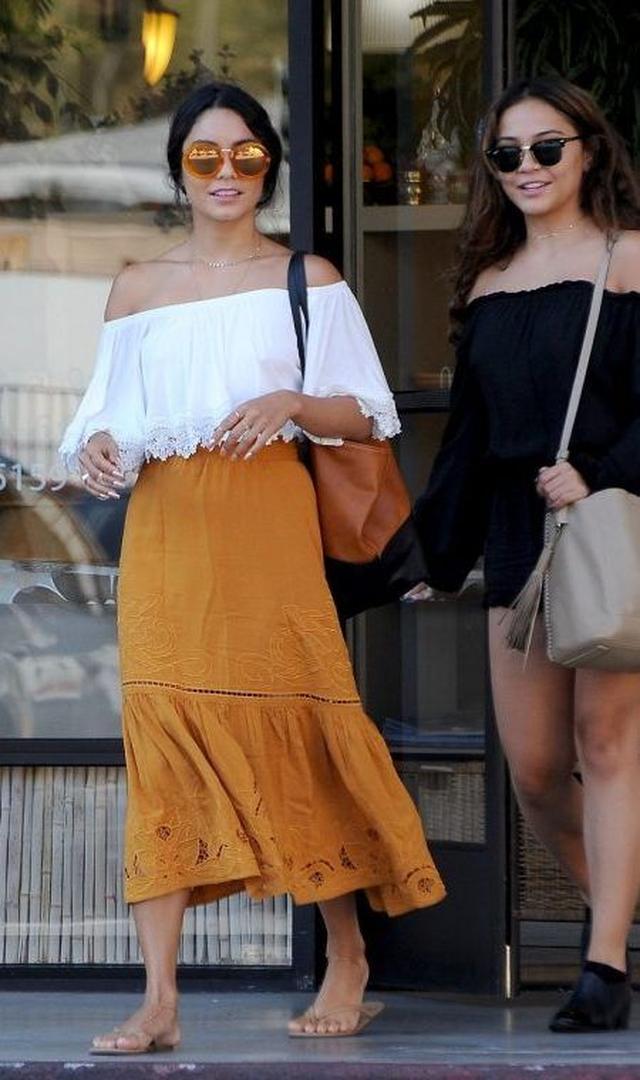 画像: 妹のステラと一緒にLAの街へ買い物に出かけたこの日は、裾にレースが配されたコットンのオフショルだートップスに繊細なカットワークが美しいマスタード色のミモレ丈スカートで。べっこうフレームのラウンドミラーサングラスでエッジを効かせて。