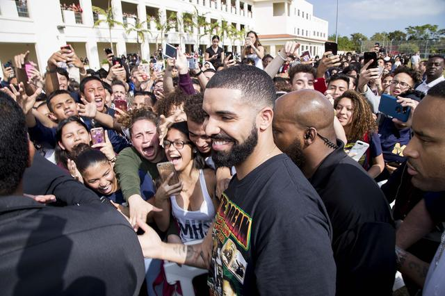 画像: 寄付を行ったマイアミ市内の高校で学生たちに崇められるドレイク。