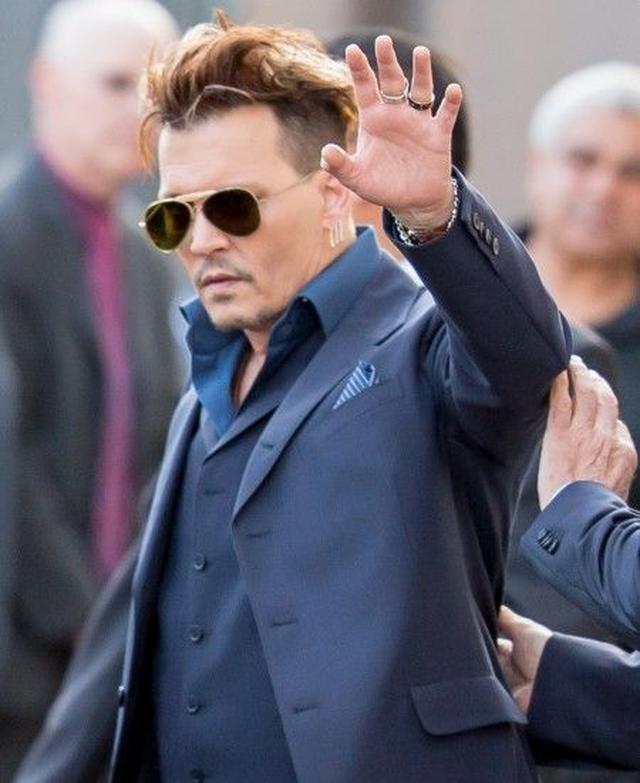 画像: 離婚を申請された翌日、TV番組の収録に現れファンに手を振るジョニー。