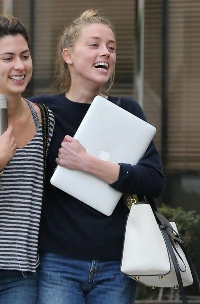 画像: 29日に弁護士と面談後、友人と笑顔で歩くアンバー。