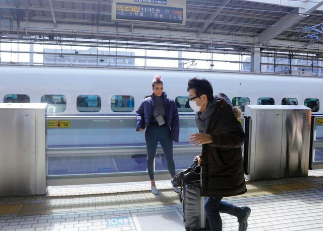 画像: 新幹線をバックにポーズを決めるキム。