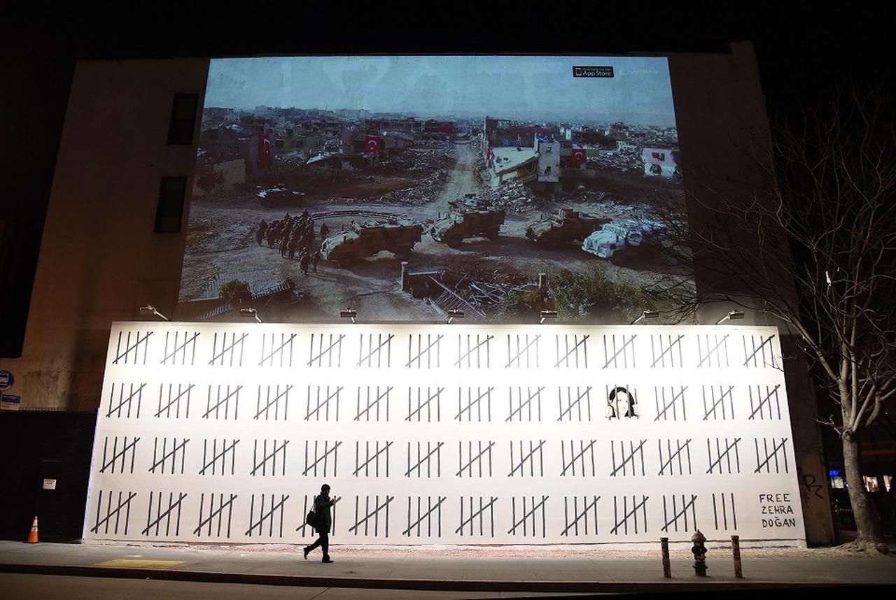 画像: バンクシーの壁画の上には、夜になるとゼフラの絵のインスピレーションとなった写真のプロジェクションが表示される。