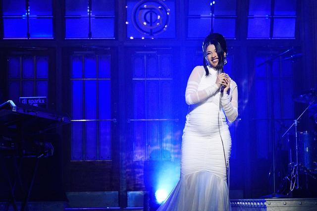 画像: この日、あえてお腹が目立つ白のタイトなドレスでステージに上がったカーディは、笑顔で会場とTVの前にいるファンに妊娠していることを報告した。