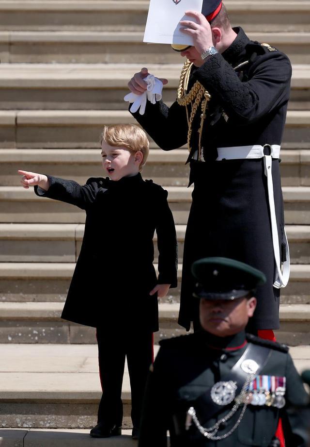 画像: 会場から出てきた時に、外の何かに気付いたジョージ王子は父ウィリアム王子に「パパ見て!」とばかりに指を差していた。