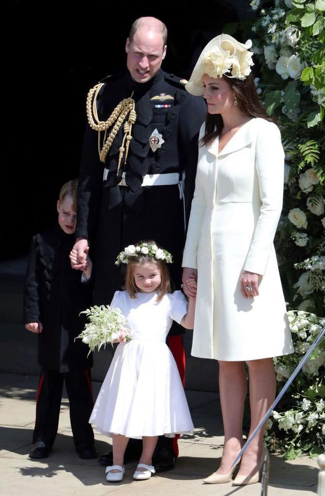 画像: ジョージ王子はシャイなのか疲れたのか、しかめっ面でウィリアム王子に寄り添って隠れる