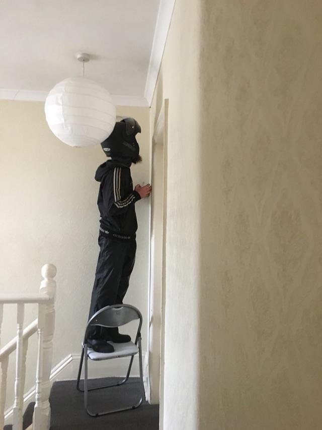 画像: 蜘蛛を退治する配達員の男性。
