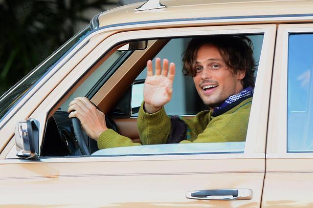画像: ヴィンテージのメルセデスのステーションワゴンのハンドルを握り、カメラに手を振るマシュー・グレイ・ギュブラー。
