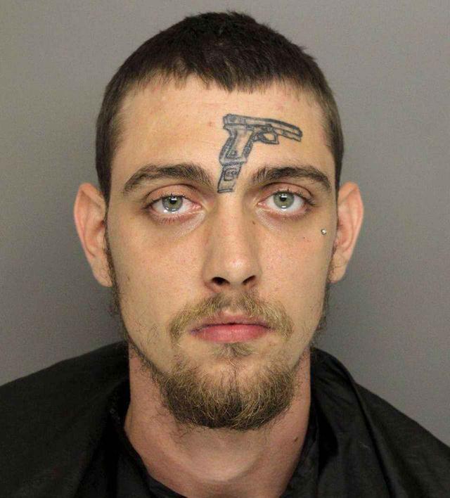 画像: 逮捕された男の額に銃のタトゥー