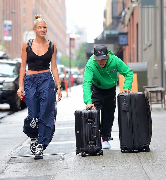 画像: 小雨のなか、ヘイリーの分のスーツケースも運んであげるジェントルマンなジャスティン。