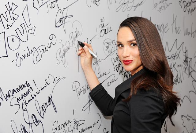 画像: 2016年の『SUITS/スーツ』のPRイベントの舞台裏でホワイトボードにフルネームでサインするメーガン。
