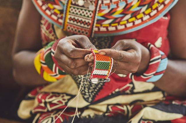 画像: サンブル族の女性がエレファントバッグのためにビーズ細工を手作業で行う姿。