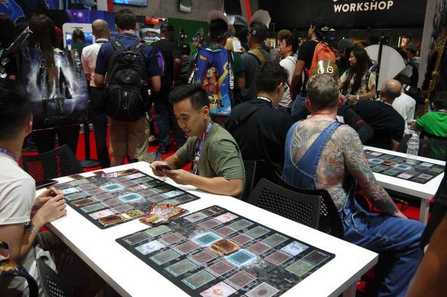 画像: 日本の会社コナミのブースには、大きな遊戯王のポスターが貼られており、ファン同士でカード対戦できる場所も。