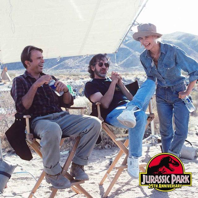 画像: ハイウエストデニムにデニムシャツをINしたスタイルで『ジュラシック・パーク』のセットに立つローラ・ダーン(右)。一緒に談笑するのは、スティーヴン・スピルバーグ監督(中央)とサム・ニール(左)。
