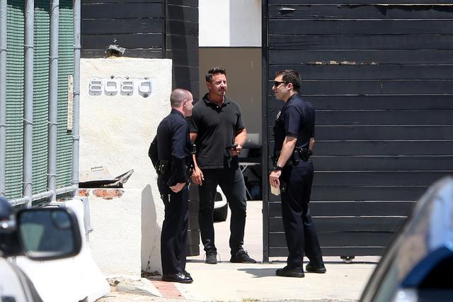 画像: 事件の2日後、デミの自宅を訪問しセキュリティ担当の男性に話を聞く警察官たち。
