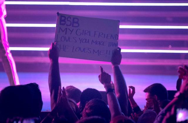 画像: バックストリート・ボーイズのレジンデンシー公演で「僕の彼女は僕より君らのことが好き」というプラカードを掲げる男性。