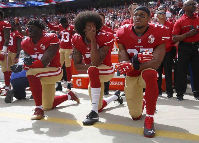 画像: サンフランシスコ・フォーティナイナーズのチームメイトと一緒にひざまずくコリン・キャパニック選手(中央)。炎上を受けて、現在NFLでは国歌斉唱中にひざまずく行為は全面禁止となっている。