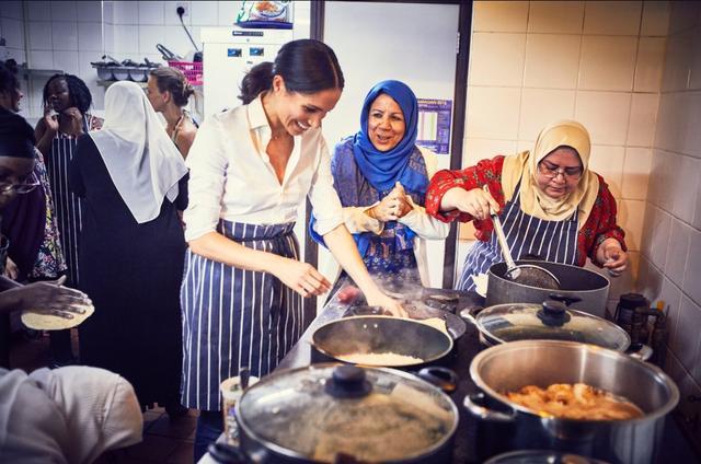 画像: ハブ・コミュニティ・キッチンの女性たちの指導の下、料理の腕を振るうメーガン妃。©Kensington Palace/ Twitter