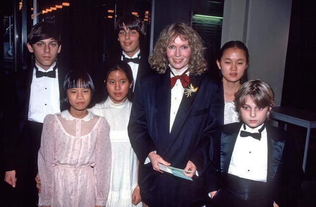 画像: 1970年代から貧困地域の子供たちを養子に迎え入れていることで知られるミア。その多くが、受け入れが難しいと思われた身体障害者だった。1985年に撮影されたミアと数名の子供たちの写真。右から2番目がスン・イー。