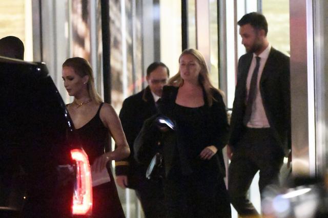 画像: ジェニファーの後ろを少し離れて歩くスーツ姿の男性がクック。