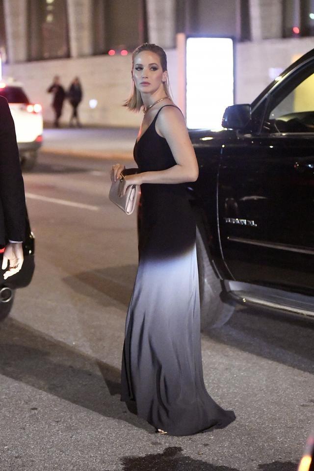 画像: シンプルな黒のスリップドレスでニューヨークの自宅からプレミア会場へと向かうジェニファー。