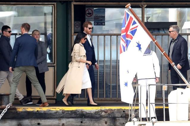 画像: 移動時、ヘンリー王子と手をつないで歩くメーガン妃はトレンチコートを羽織り、足元には黒のフラットシューズを履いていた。
