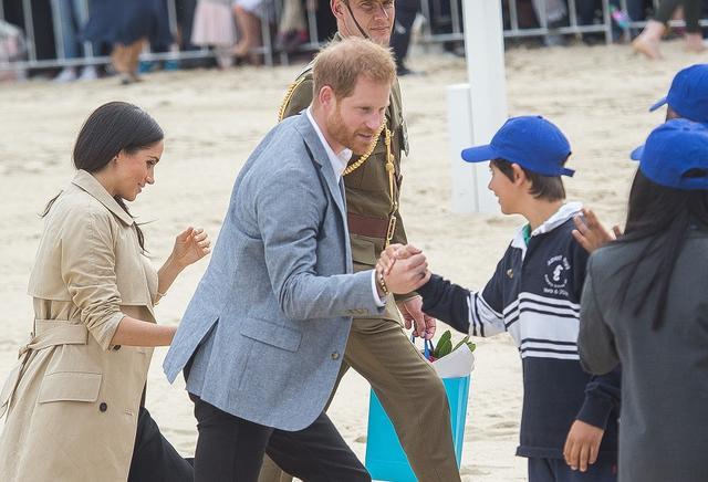 画像: 子供とガッチリ握手を交わす右手にもやはり「黒い指輪」。