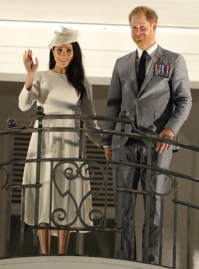 画像: ホテルのバルコニーから集まった群衆に手を振る夫妻。