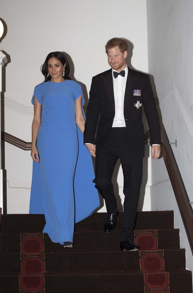 画像: 晩餐会には正装で出席。メーガン妃はロイヤルブルーのSafiyaa(サフィア)のケープドレスを着用し、ふっくらとしたお腹のラインをのぞかせていた。