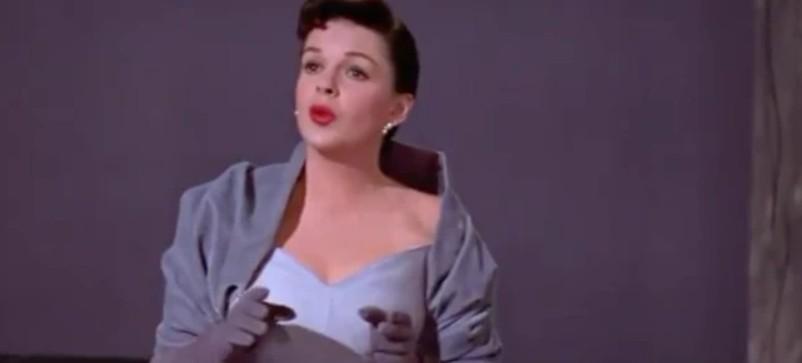 画像: ジュディ演じるエスターは、ドレスの上に一段階暗めの色のケープを羽織り、ロンググローブを着用。©Broadway Classics/Youtube www.youtube.com