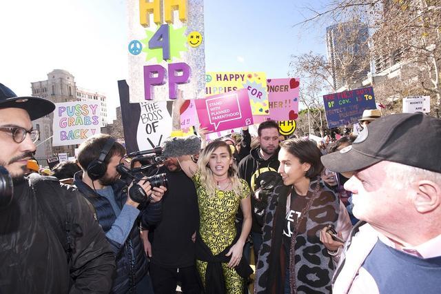 画像: 2017年ロサンゼルスで行われたウィメンズ・マーチに「PP(Pussy Powerの略)」と書かれたプラカードを掲げて参加するマイリー。