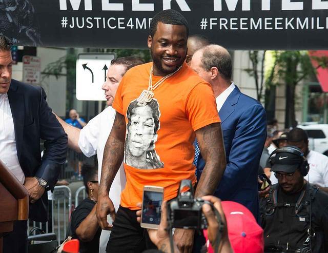 画像: 警察に暴行されたとされる跡が顔面に残る当時のマグショットがプリントされたTシャツを着用したミーク。