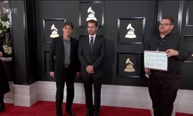 画像: 右のスタッフがアーティストの名前を持っている様子。