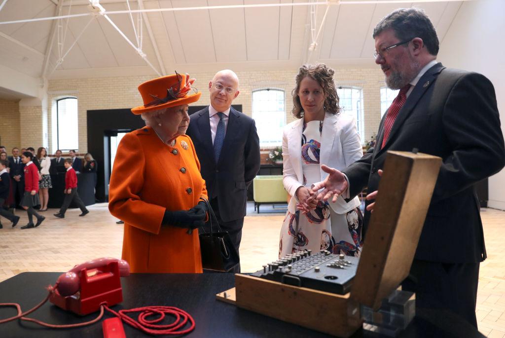 画像: サイエンス・ミュージアムの職員たちから展示物について説明を受けるエリザベス女王。