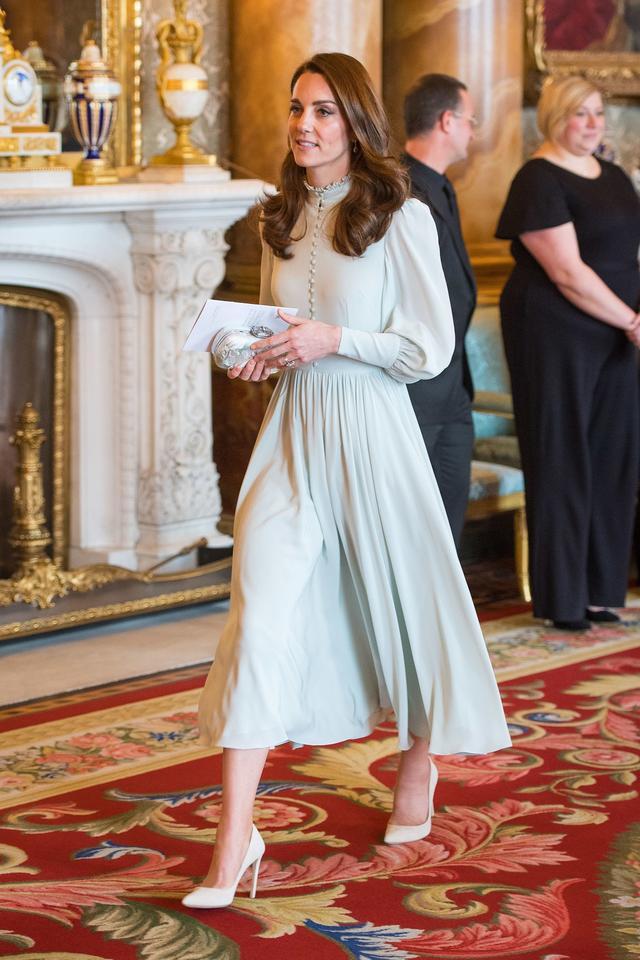 画像: フリルがついたハイネックに、たくさんのくるみボタンがついたフェミニンでクラシカルなパフスリーブのドレスを身に着けて。