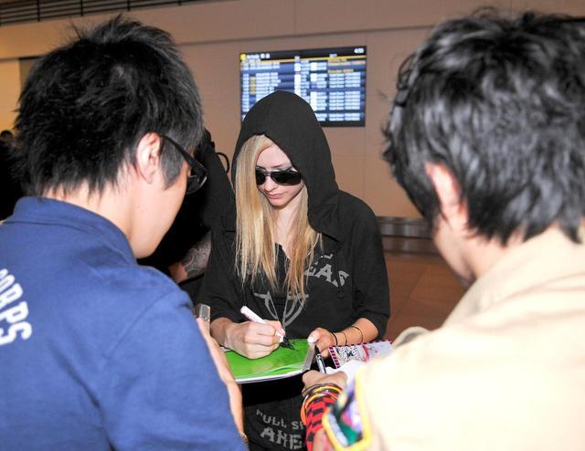 画像: サマーソニックのため2011年に来日したときに、羽田空港でファンのサインのお願いにこたえるアヴリル。