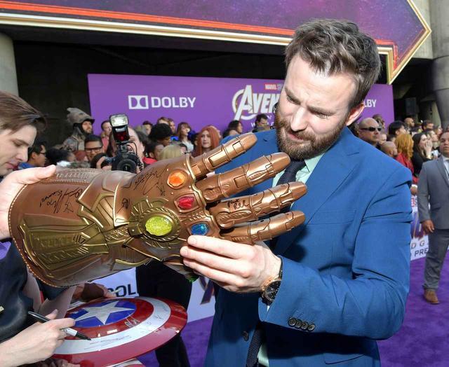 """画像: ファンが持ち込んだ""""インフィニティ・ガントレット""""にサインをするクリス・エヴァンス。"""
