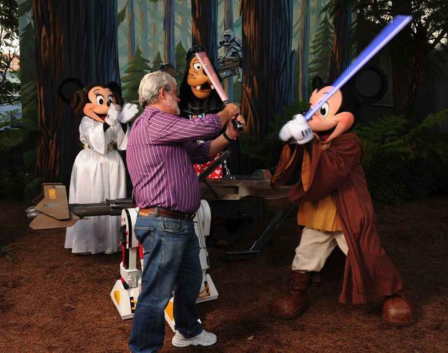画像: シリーズ1作目と新3部作の監督を務めたジョージ・ルーカスと、『スター・ウォーズ』のコスプレをしたミッキーマウスとその仲間たち。