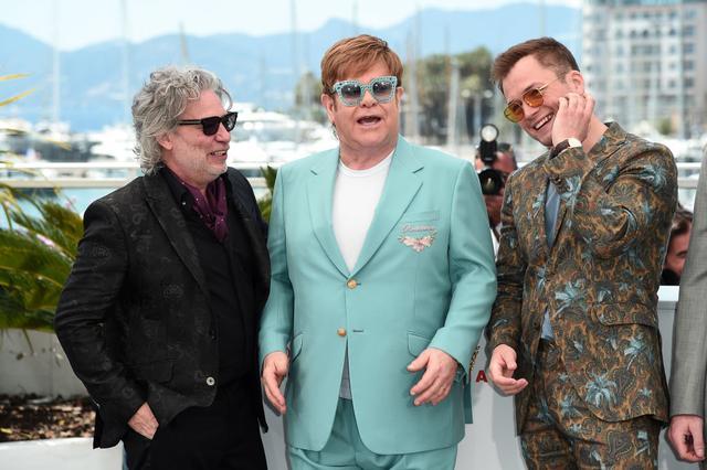 画像: 『ロケットマン』の物語の題材となったシンガーのエルトン・ジョン(中央)や主演のタロン・エガートン(右)とともにカンヌ国際映画祭のプレスイベントに登場したデクスター・フレッチャー監督(左)。