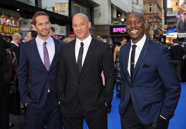 画像: ブライアン役のポール・ウォーカーとドム役のヴィン・ディーゼル。2013年に行なわれた『ワイルド・スピード EURO MISSION』のロンドン・プレミアにて。右はローマン役の対リース・ギブソン。