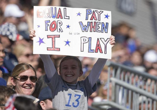 画像: 私が選手になる時には平等な賃金を、と訴えるプラカードを掲げるキッズファン。