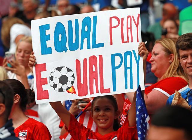 画像: 女子サッカーW杯アメリカ対イングランド戦で「同等のプレー、同等のペイ」というプラカードを掲げるファン。